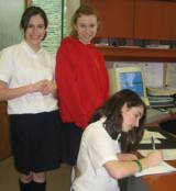 Karlee (left) and Sara (standing) wait while Danielle signs up.