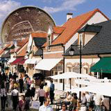 The Euro peeks from behind tile roofs at a market.